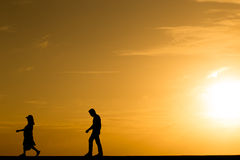 Silhouette people walking at sunset. With orange color filtered Stock Image