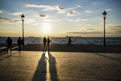 Silhouette of people walking at sunset by sea. Stock Photography