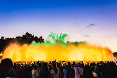 Silhouette of people watching at colorful illuminated musical fountains in the evening. Light and water night show performance. Montjuic Magic Fountain stock images
