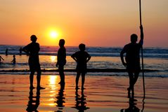 Silhouette people watching the sunset. By the beach Stock Images