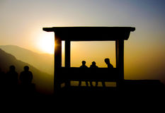 Silhouette of people watching sunset. Silhouette of people enjoying the sunset sitting in a shade Royalty Free Stock Photography