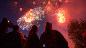 Silhouette of people who watch the fireworks in the night sky. stock footage