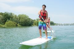 Silhouette perfect couple engage standup paddle boarding Stock Photo