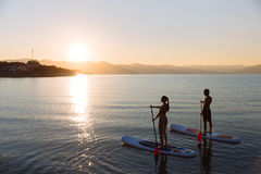Silhouette of perfect couple engage standup paddle boarding Stock Image