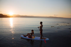Silhouette of perfect couple engage standup paddle boarding Stock Images