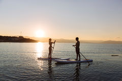 Silhouette of perfect couple engage standup paddle boarding Royalty Free Stock Photography