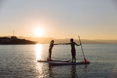 Silhouette of perfect couple engage standup paddle boarding Stock Photography
