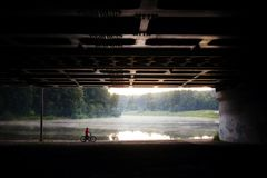 Person on bicycle by the water under the bridge. Silhouette of person on bicycle by the water with suspension bridge stock photography
