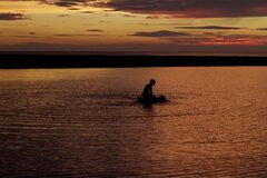 Silhouette of Person on Body of Water during Sunset Royalty Free Stock Photo