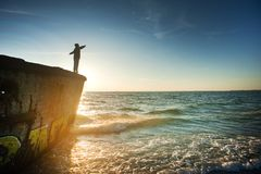 Silhouette of Person on Cliff Beside Body of Water during Golden Hour Royalty Free Stock Images