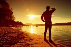 Silhouette of the person on a decline seeing off the sun. Slim sportsman on beach shadowing eyes . Stock Image