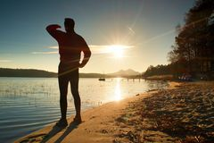 Silhouette of the person on a decline seeing off the sun. Slim sportsman on beach shadowing eyes . Stock Photo
