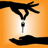 Silhouette person drops car key into a cupped hand Stock Images