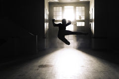 Silhouette of A Person Flying Kick Inside A Room Royalty Free Stock Photos