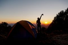 The silhouette of a person is happy with holding a coffee cup near the tent around the mountain. stock photography