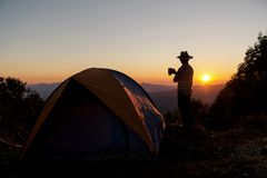 The silhouette of a person is happy with holding a coffee cup near the tent around the mountain. royalty free stock image