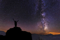 Silhouette of the person. On the high rock at Milky Way background Stock Image