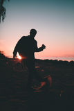 Silhouette of the person holding in hand drink in a bottle. Outdoors photo Royalty Free Stock Photo