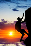 Silhouette of a person without insurance climbs the rock. In the background of the sunset Royalty Free Stock Photo