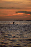 Silhouette of person kayaking at sea during sunset.  Royalty Free Stock Image