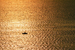 Silhouette of a person lost at the ocean. Silhouette of unrecognizable person on a rowboat lost at the ocean Stock Photo