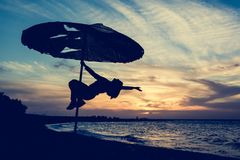 Silhouette of a person on a parasol on a beach. Stock Images