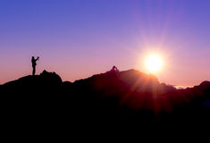 Silhouette of a person photographing sunrise. Silhouette of a photographer shooting sun rising above the mountains Stock Images