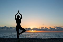 Silhouette of person doing yoga on the beach at sunrise royalty free stock photos