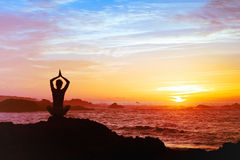 Silhouette of person practicing yoga Stock Photo