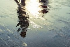 Silhouette of a person reflecting in a puddle after the rain. Silhouette of a person reflecting in a puddle after the rain royalty free stock photo