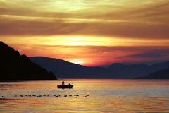Silhouette of Person Riding Boat on Body of Water during Sunset Stock Images