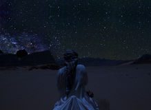 Silhouette of a person riding the camel beneath the stars, Milky Way and a lot of stars over the mountain at Wadi Rum desert. Sky at night in summer, concept Royalty Free Stock Images