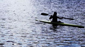 A silhouette of a person rowing a canoe stock footage