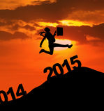 Silhouette person run to chase her dream. Silhouette businesswoman carrying briefcase jumps on the hill at sunset to chase her dream in future 2015 Royalty Free Stock Photos