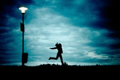 Silhouette of Person Beside Silhouette of Street Light Stock Photography
