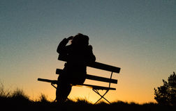 Silhouette of a person sitting on a bench in sunset. Silhouette of a person sitting on a bench during in sunset. Simple picture Stock Photo