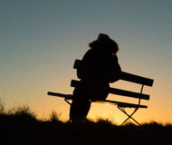 Silhouette of a person sitting on a bench in sunset. Silhouette of a person sitting on a bench during in sunset. Simple picture Royalty Free Stock Image