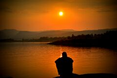 Silhouette of Person Sitting Beside Body of Water Stock Photography