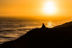Silhouette of Person Sitting on Mountain Facing on Body of Water during Golden Time Royalty Free Stock Photo