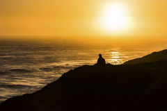Silhouette of Person Sitting on Mountain Facing on Body of Water during Golden Time Royalty Free Stock Image