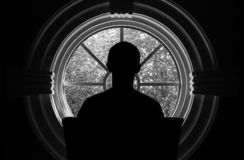 Silhouette of a person sitting near a round window with his back to the camera royalty free stock photos