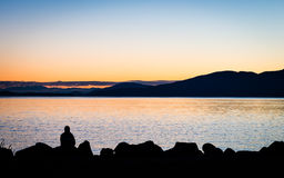 Silhouette of a person sitting on rocks watching the sunset. Silhouette of a person sitting on rocks watching the sunset over the water Stock Photo