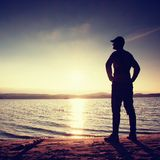 Silhouette of person in sportswear on beach seeing into morning Sun Stock Photo