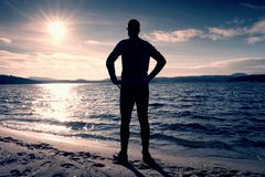 Silhouette of person in sportswear and short hair  on beach see into Sun above sea Stock Photos