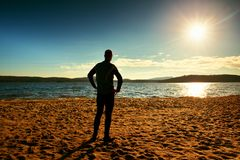 Silhouette of person in sportswear and short hair  on beach see into Sun above sea Royalty Free Stock Photos