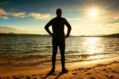 Silhouette of person in sportswear and short hair  on beach see into Sun above sea Stock Photo
