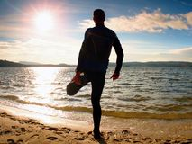 Silhouette of person in sportswear and short hair  on beach see into Sun above sea. Silhouette of person in sportswear and short hair on beach seeing into Royalty Free Stock Photography