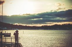 Silhouette of Person Standing on Dock Stock Image