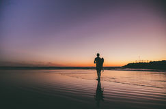 Silhouette of a Person Standing on Shore during Sunset Royalty Free Stock Photo