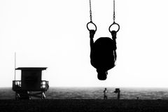 Silhouette of a person swinging on rings Stock Images